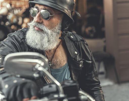 Älterer Biker mit grauem Vollbart und Sonnenbrille auf seiner Harley - auf dem Weg ins Holiday Inn Hamburg